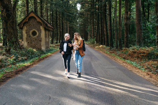 Two women walking down the road looking at their phone