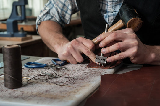 Close up of leather craftsman hands working with natural leather using hammer. Handbag master at work in local workshop. Male shoemaker creating handmade product