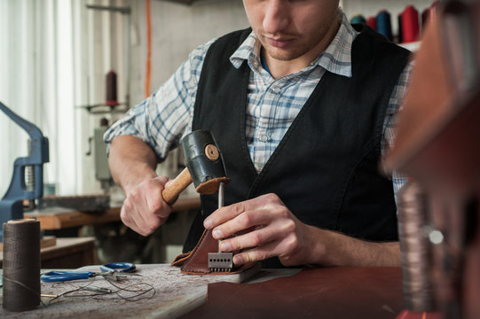 Close up of leather craftsman working with natural leather using hammer.