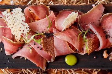 Antipasto on wooden plate close up. Cold smoked meat plate with tomato hot sauce, sliced ham, prosciutto, bacon. Appetizer on wooden tray cut tree sawed imitation.
