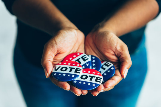 Black hands holding vote buttons