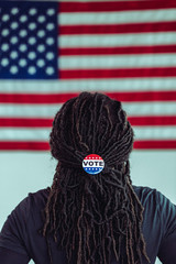 Black citizen looking at American Flag with Vote button