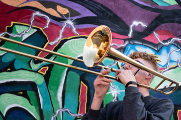 High school jazz band trombone player by colorful graffiti
