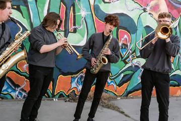 High school jazz band brass musicians by graffiti mural