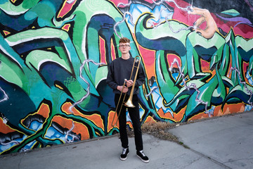 Portrait of high school jazz band trombone player by colorful graffiti