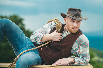 Sexy masculine stylish cowboy macho man holding lasso rope. Western style men fashion. Handsome cowboy in plaid shirt at beautiful rural nature background. Wall mural