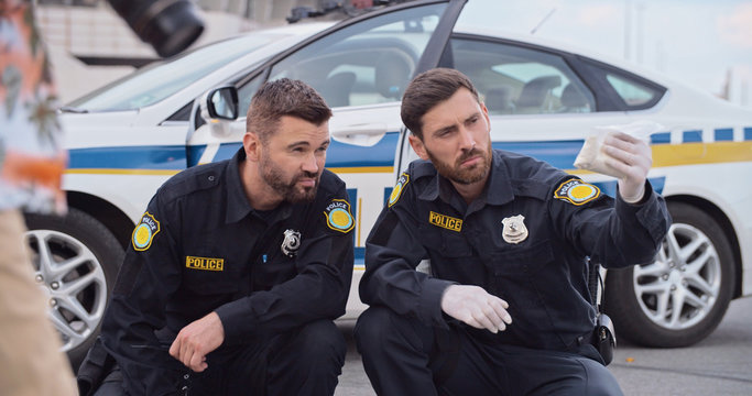 Police officers investigate an accident collect evidence in crime area. Two handsome serious policemen at work finding drugs on the ground squatting near police patrol car.