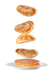 Plate with falling pancakes on white background