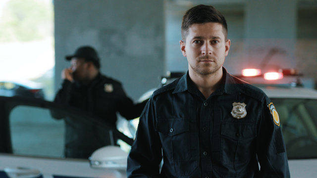 Portrait serious young man cops stand near patrol car look at camera enforcement background his colleague happy officer police uniform auto safety control policeman close up slow motion
