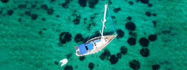 Aerial drone ultra wide photo of sail boat docked in tropical exotic bay with emerald coral reef