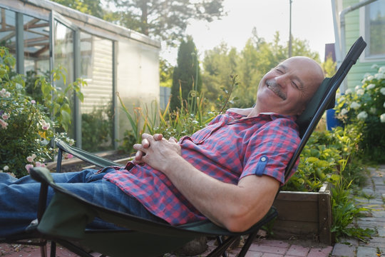 Adult man in casual clothing sitting in a deck chair and resting having a nap.