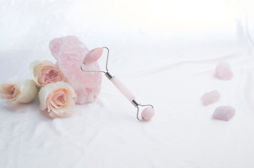 Rose quartz crystal facial roller and pink roses