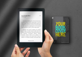 Hands Holding E-Reader with Book in the Background Mockup