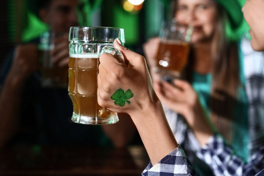 Young woman with friends celebrating St. Patrick's Day in pub