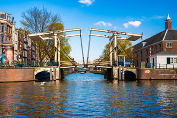 Fotomurales - Stunning view of Amsterdam canals and typical dutch houses with narrow cosy streets filled with bicycles in the capital of Netherlands, Europe on a beautiful sunny day.