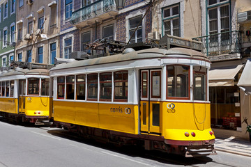 LISBON, PORTUGAL - JUNE 22, 2013: Yellow trams of the Route #28 on the street of Lisbon. It is one of the most popular routes by tourists. Lisbon tramway network operates since 1873