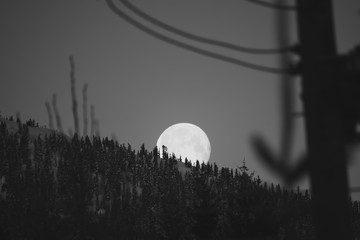 A picture of the moon peeking out from behind some mountains.   Whistler BC Canada