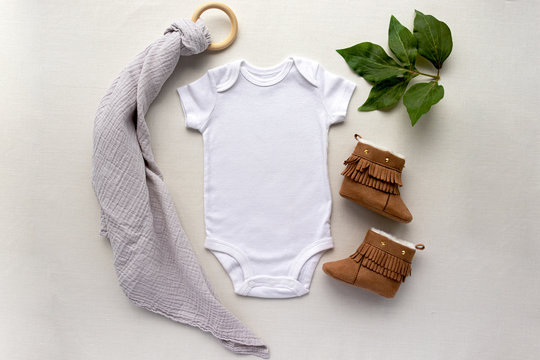 Blank gender neutral white baby bodysuit close up - with leaves and brown booties - newborn apparel mockup