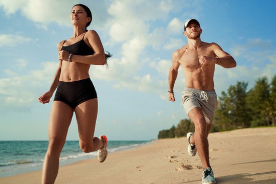 Healthy lifestyle. Jogging outdoors. Young man and woman is running on the sand beach.