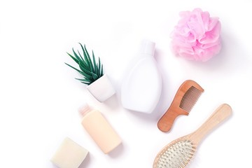 White shampoo bottle, hair balm, natural soap, wooden comb, aloe vera and pink sponge. Organic spa cosmetic flat lay photo