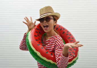 Happy young asian woman wearing red stripped shirt, sunglasses and straw hat in watermelon inflatable ring standing over white wall background, Business summer holiday concept