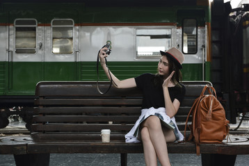 Young beautiful woman traveler taking selfe at camera sitting on wooden old chair with backpack and coffee cup in train station, Business travel holiday relaxation concept