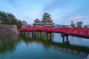 Wall Mural - Matsumoto Castle at twilight with the red bridge in Nagano, Japan.