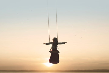 special contact between nature and a woman with open arms on a swing Fotomurales