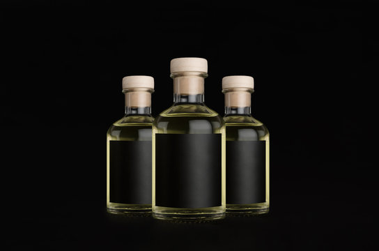 Luxury three glass bottles for cosmetic, perfume, drink with black label, cork, yellow liquid on dark black background, mock up for design of product.