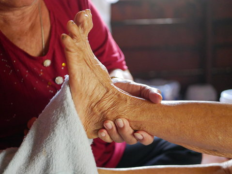 Hands of a woman holding an older person's feet, while gently wiping / cleaning it with a wet washcloth - giving an elderly a bed bath at home