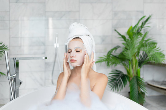 Young woman applying cosmetic face sheet mask while taking bath. Pretty girl wearing towel on head sitting in bathtub with soap foam. Beauty spa cleansing procedure. Home bathroom interior