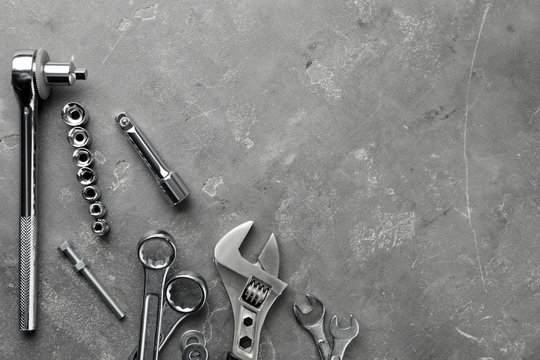 Auto mechanic's tools on grey stone table, flat lay. Space for text