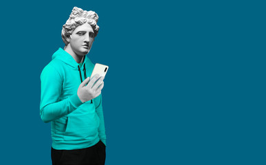 Modern art collage. Concept portrait of a man  holding mobile smartphone using app texting sms message. Gypsum head of of Apollo. Man in suit. On a blue background.