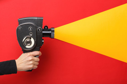 Female hand holding old style film movie camera imitating shooting process on a red background
