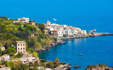 Ischia Ponte bordering waters of Bay of Cartaromana and Guevara Tower on Ischia Island, Italy.