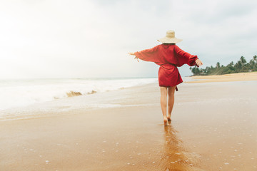 Sunny picture of lonely young woman walking alone along seashore or ocean coast on island. Hold hands aside of body. Good weather and time for vacation.