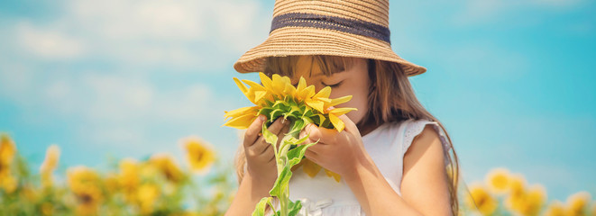 A child in a field of sunflowers. Selective focus.