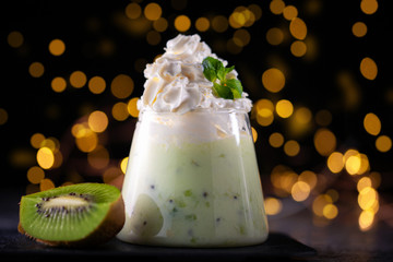 Fresh homemade yogurt in a glass with kiwi. Lights on the background.