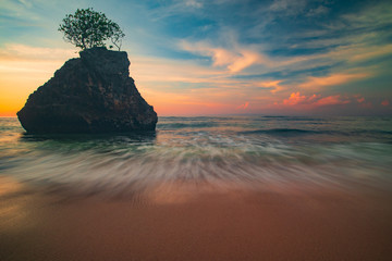 Amazing seascape. Beach during sunset. Rock with tree in the ocean. Slow shutter speed. Bingin beach, Bali