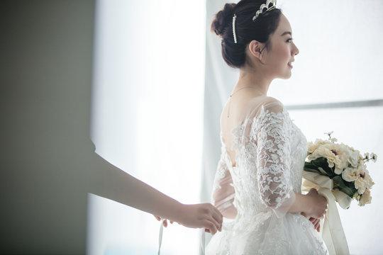 bridesmaids fasten wedding dress with zipper