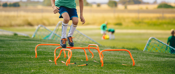 Low section portrait of unrecognizable boy jumping over hurdles in football field. Kid young athletes training with football equipment. Soccer speed durability training