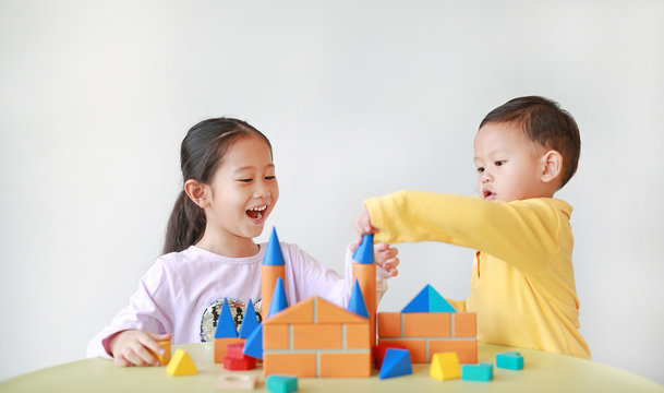 Happy asian little child girl and baby boy playing a colorful wood block toy on table over white background. Sister and her brother playing together.