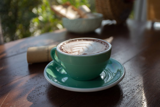 A green cup of coffee placed on a wooden table by the window in a coffee shop, Concept: Delicious breakfast drinks fragrant suitable for lifestyle, closeup cup of coffee over the top with space