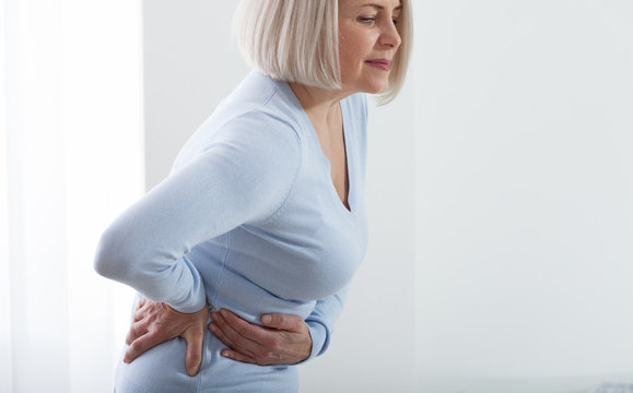 Woman in pain holding her stomach on the right side