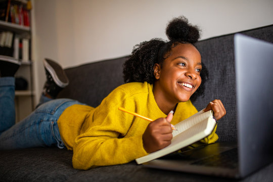 happy african american girl student looking at laptop computer screen at home