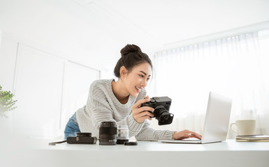 Portrait of beautiful asian photographer woman working in office holding camera with laptop. Business people employee freelance online marketing.  Successful freelance creative artist girl business Fotobehang