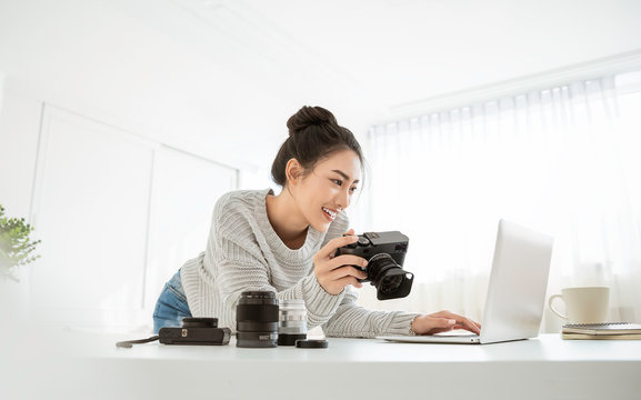 Portrait of beautiful asian photographer woman working home office holding camera with laptop. Business people employee freelance online marketing.  Successful freelance creative artist girl business