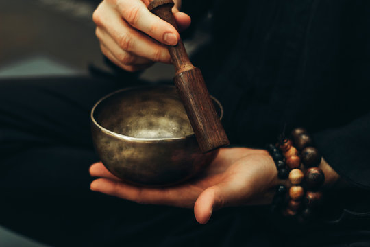 Close-up of hands with rosary playing on singing bowls. Relaxation and meditation. Alternative medicine. Tibetan and Himalayan singing bowls. Make a sound.