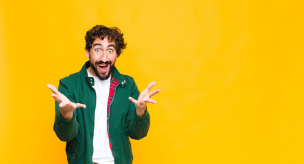 Obraz young crazy bearded man feeling happy, astonished, lucky and surprised, like saying omg seriously? Unbelievable against flat wall - fototapety do salonu