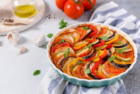 Ratatouille casserole on white background. Colorful layers of fresh summer vegetables: zucchini, eggplant, tomatoes and potatoes. Healthy vegan, vegetarian dish. Side view, copy space. Menu, recipe